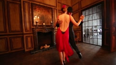 Girl in red dress and man in black suit dance tango in two rooms - stock footage