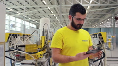 Camera pans across to create a Portrait of factory worker using a tablet Stock Footage