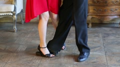 Legs of woman in red and man in black dancing tango in retro room Stock Footage