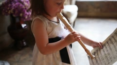 Close up of little girl in dress playing flute and holding notes Arkistovideo