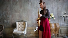 Girl with long hair playing saxophone in beautiful room with candles Stock Footage