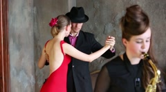 Couple dancing tango near girl playing saxophone. Girl out of focus Stock Footage