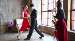 Couple dancing tango and girl playing saxophone near window Stock Footage