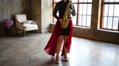 Girl in red skirt plays saxophone in retro room with wind Stock Footage