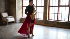 Girl in red skirt plays saxophone in retro room near window Stock Footage