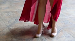Legs of girl in heels and red skirt in room with wind Stock Footage