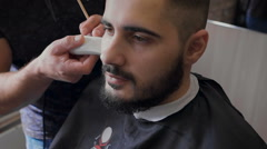 Young hipster with your stylist. Barber works with client beard, with a trimmer Stock Footage