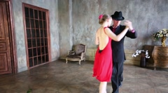 Young couple dances tango in retro room with rose on floor Stock Footage