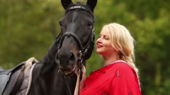 Woman in red dress and blond hair stands near horse Stock Footage