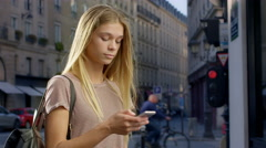 Young lady uses phone to negotiate her way around the city. - stock footage