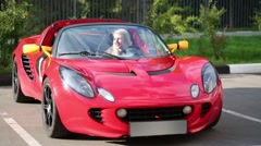 Blonde woman sits in modern red sport car at sunny day Stock Footage