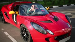 Blonde woman sits in red sport car and talks phone at sunny day Stock Footage