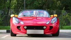 Blonde woman sits in red sport car looks in mirror at sunny day Stock Footage