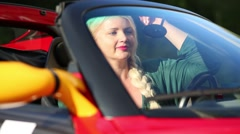 Blonde woman in red sport car looks in mirror and keeps wheel Stock Footage