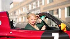 Blonde young woman poses in red sport car at summer day Stock Footage