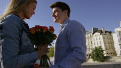 Young man gives his lady a bunch of roses and a big kiss while in Paris Stock Footage