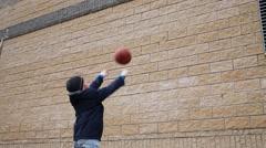 Boy training to play basketball near brick wall outdoor Stock Footage