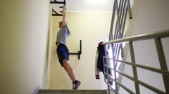 Young man trains on horizontal bar in staircase of building Stock Footage