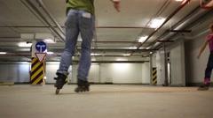 Two men and girl roller skate in indoor underground parking Stock Footage