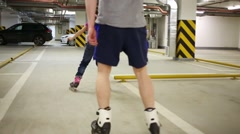 Back of man and girl roller skating in indoor underground parking Stock Footage
