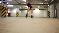 Legs of man roller skating and braking in underground parking Stock Footage