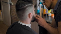 Fashion barbershop or salon hairstyles. Master works with a beard young man Stock Footage