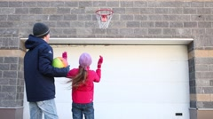 Back of boy and girl playing with balls and basketball hoop outdoor Stock Footage