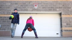 Boy and girl play with balls and basketball hoop near automatic gates Stock Footage