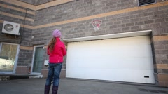 Back of boy and girl playing with balls and basketball hoop Stock Footage