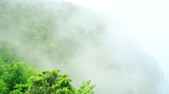 Clouds pass over mountain. Green hillside with trees in cloud scraps. Stock Footage
