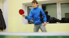 Happy boy teenager in blue plays table tennis indoor Stock Footage