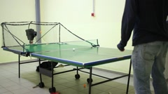 Part of body of man playing table tennis with robot Stock Footage