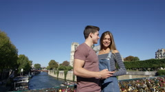 Camera moves through shot as a young couple take a selfie infront of Natre Dame Stock Footage