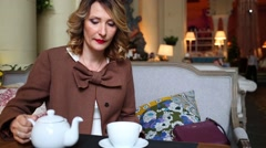 Woman in jacket pours tea from white teapot in restaurant Stock Footage