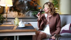 Woman drinks red wine and removes jacket in cozy restaurant - stock footage
