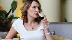 Middle-aged woman drinks red wine in cozy restaurant - stock footage