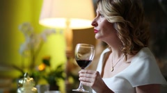 Curly woman drinks red wine in restaurant at evening Stock Footage