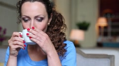 Pretty curly woman drinks tea and talks in restaurant Stock Footage
