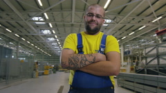 Camera moves around factory worker in warehouse Stock Footage