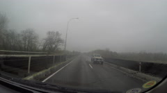 Driving across bridge on road in heavy rain point of view (pov) - stock footage