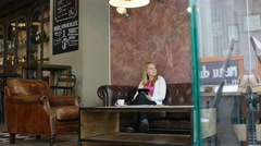 Girl drinking coffee in trendy coffee shop, while checking her tablet Stock Footage