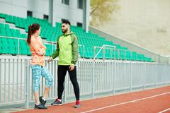 Sporty young couple in active-wear having talk at stadium Stock Photos