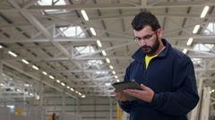 Factory worker using a tablet for work. Stock Footage