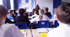 4k, Group of school kids sitting and listening to teacher in classroom from back Stock Footage