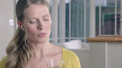 Lady taking a sip of Herbal tea while at home listening to music through her - stock footage
