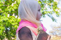 The girl in a scarf .Studying of the Bible on fresh air Stock Photos