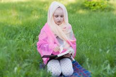 The girl in a scarf . Studying of the Bible on fresh air - stock photo