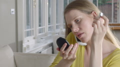 Lady uses mobile Phone while applying make up Stock Footage