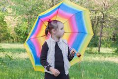 The girl with a multi-colored umbrella. Stock Photos
