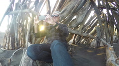 Man sitting in driftwood hut on beach taking photos with smart phone Stock Footage